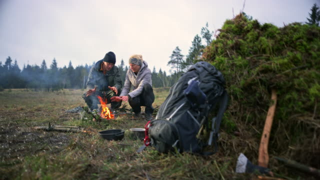 male and female wilderness survival expert warming up by the fire they lit in nature - survival stock videos and b-roll footage