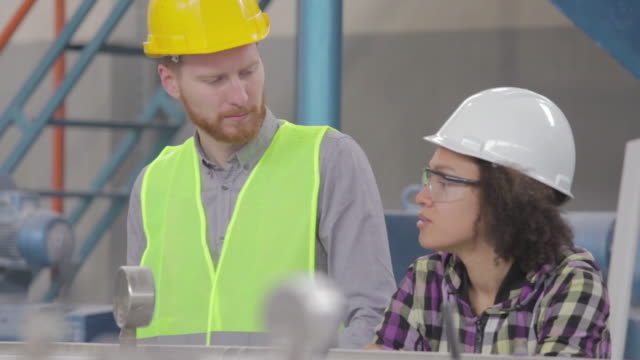 Male and female worker in the factory working and talking