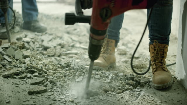 male and female worker using jackhammers to chop away the concrete floor in a house - pneumatic drill stock videos & royalty-free footage