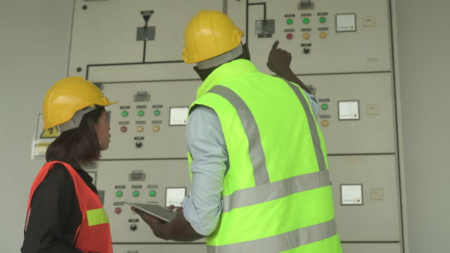 vidéos et rushes de panneau de dispositif de commande de mâle et de femelle de ouvriers dans l'atelier d'usine - switch