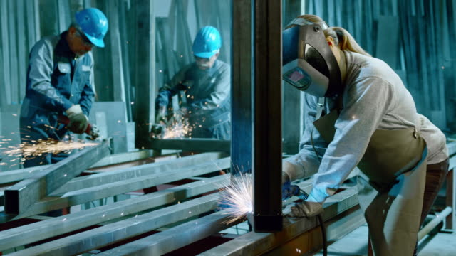 SLO MO LD Male and female workers cutting metal