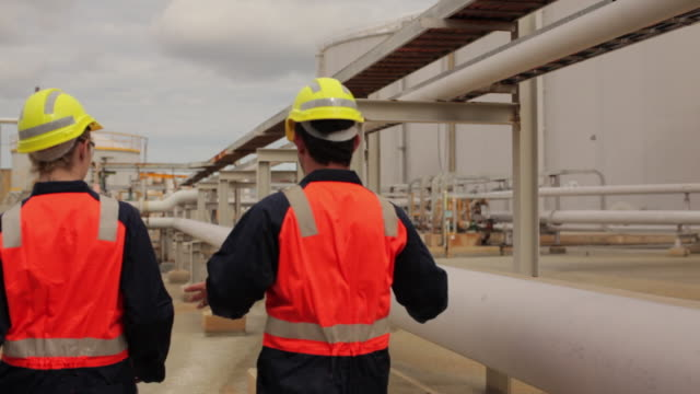 ws male and female workers talking on refinery grounds / perth, australia - safety stock videos & royalty-free footage