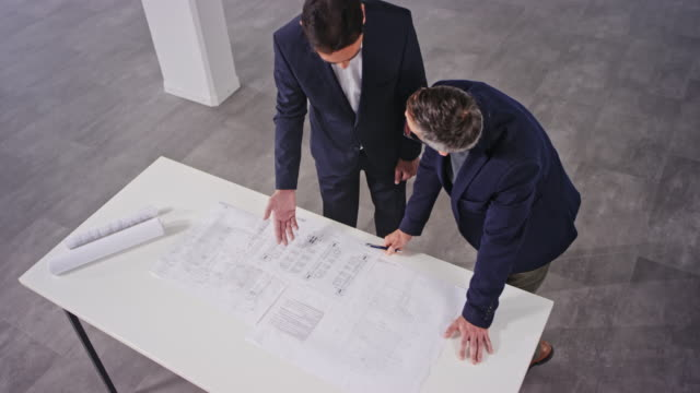 CS Male angel investor and a male interior architect talking while leaning over the plans in an empty office space