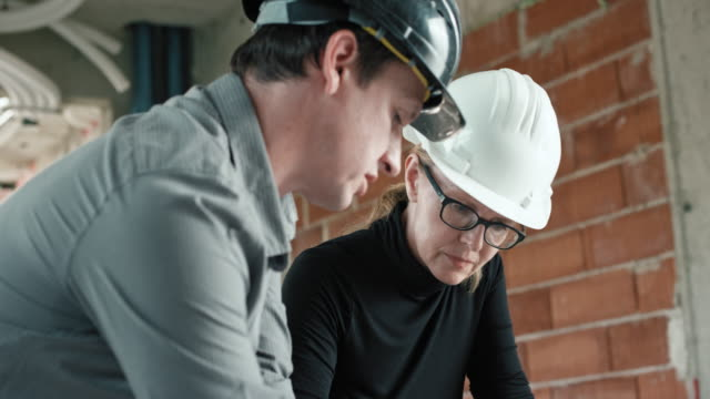 male architect and female engineer checking the details on the plan at the construction site - headwear stock videos & royalty-free footage