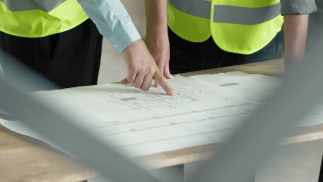 Male architect explaining details of the plan to the investor at the construction site