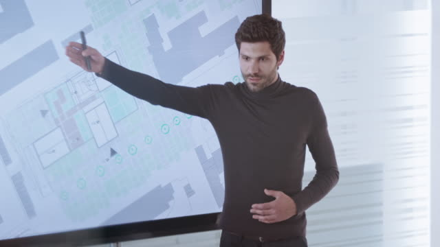 male architect explaining plan details shown on the large screen in conference room - standing stock videos & royalty-free footage