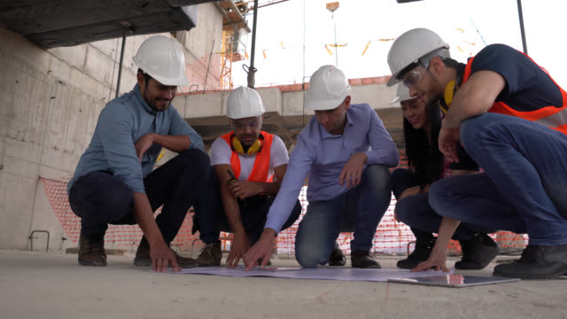 male architect giving instructions to his team all kneeling on the floor while looking at a blueprint - flooring stock videos & royalty-free footage