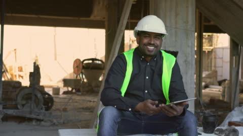 vídeos y material grabado en eventos de stock de arquitecto masculino sosteniendo tableta digital en el sitio - material de construcción