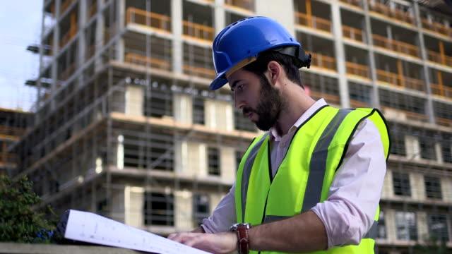 vidéos et rushes de male architect looking blueprint at construction site - un seul homme d'âge moyen