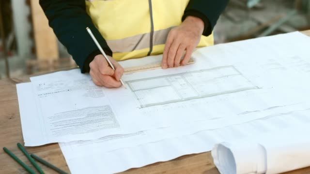 Male architect making changes to the building plans at the construction site