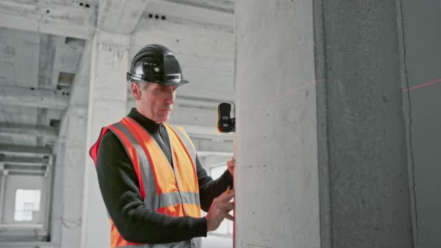 architetto maschio che misura il fascio di supporto in un edificio industriale e lo marca - misurare video stock e b–roll