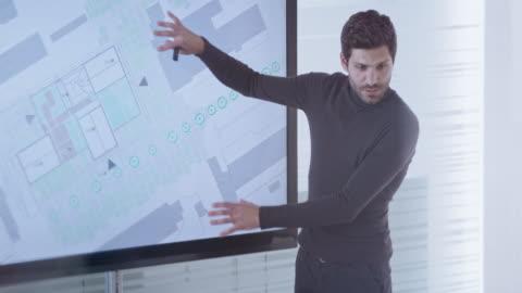männliche architekten zeigt plandetails zu seinen kollegen auf einer großbildleinwand im konferenzraum - zeigen stock-videos und b-roll-filmmaterial