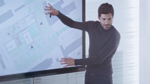male architect showing plan details to his colleagues on a wide screen in the conference room - architect stock videos & royalty-free footage