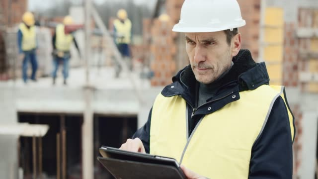 male architect standing at the construction site and checking the plans on the digital tablet - construction site stock videos & royalty-free footage