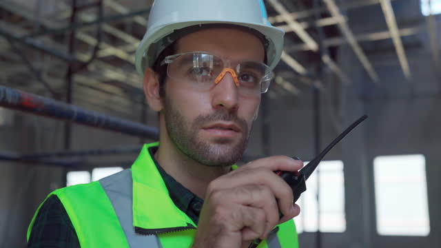 stockvideo's en b-roll-footage met male architect standing at the construction site and checking the plans supervise work. - hoofddeksel