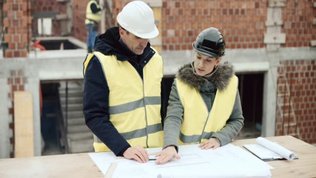 Male architect talking to the female investor standing at the construction site and discussing the plans on the table