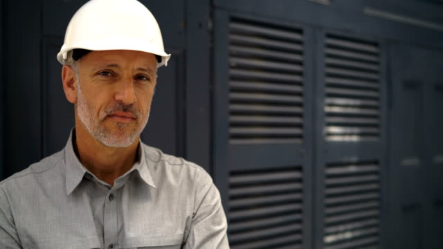 Male architect wearing hardhat in office