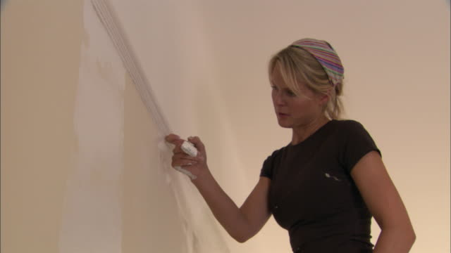 Male arm using paint roller and woman using paint brush to paint wall