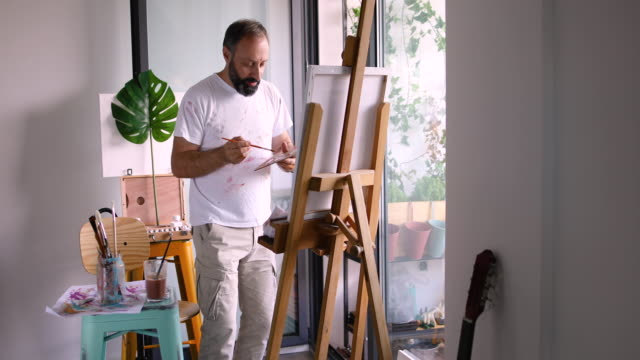 vídeos de stock, filmes e b-roll de artista masculino dançando na pintura em estúdio - homens maduros