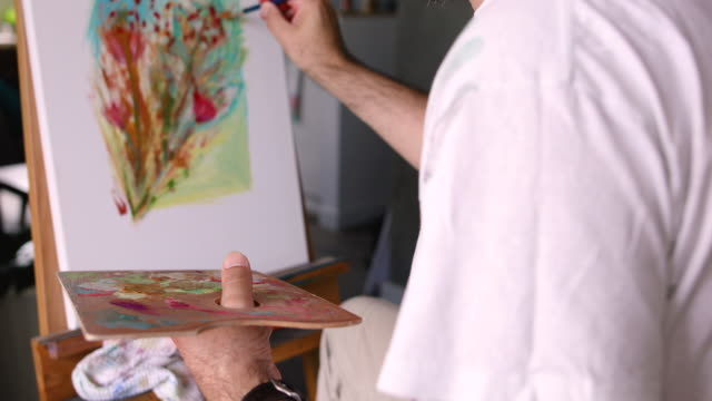 male artist working on painting in studio - only mature men stock videos & royalty-free footage