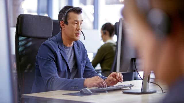 ld male asian call center agent bietet kundensupport an seinem arbeitsplatz - headset stock-videos und b-roll-filmmaterial