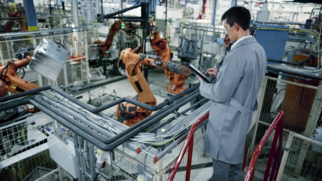 ld male asian engineer inspecting the work process of the robots performing their operations in the factory - attrezzatura industriale video stock e b–roll