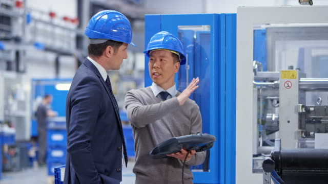 ds male asian factory employee presenting the machine capabilities to the caucasian businessman - pannello di controllo video stock e b–roll
