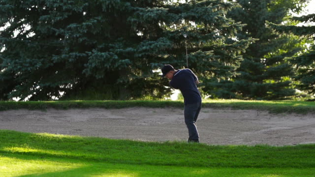 vidéos et rushes de male asiatique golf arrive dans un bunker - swing de golf