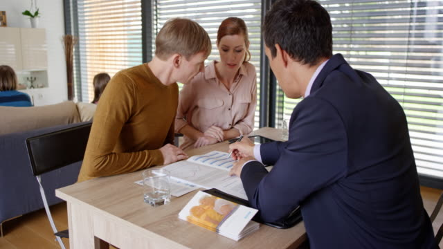 Male Asian personal banker advising couple in their home