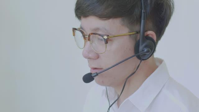 雄アジアの電話、留守番電話、電話オペレーター - ヘッドセット点の映像素材/bロール