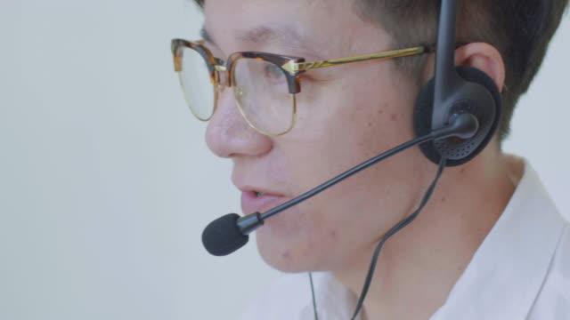 Exploitant van de mannelijke Aziatische telefoon een oproep beantwoorden
