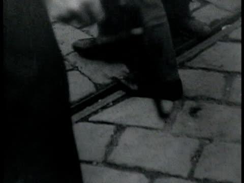 male assassin in suit w/ hand down by side walking holding pistol walking through crowd - pistole stock-videos und b-roll-filmmaterial
