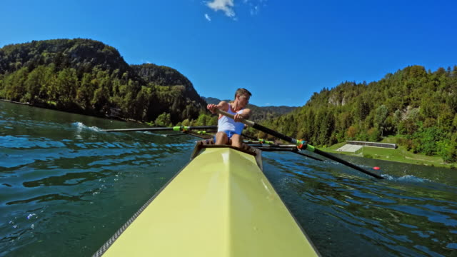 pov male athlete and his team mate rowing in a coxless pair on a sunny day - canottaggio senza timoniere video stock e b–roll