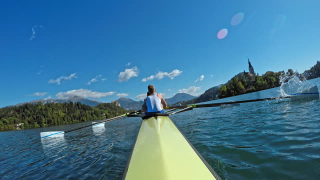pov male athlete and his team mates rowing on the lake in sunshine - rowing stock videos & royalty-free footage