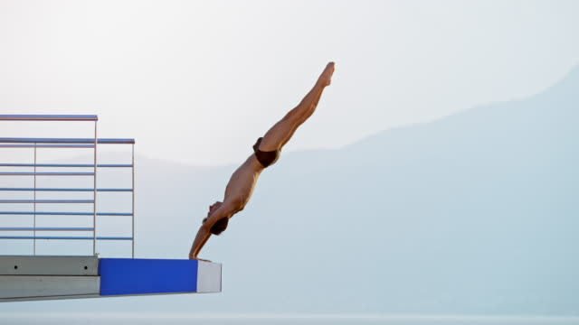slo mo male athlete diving from a high platform at a competition - scrittura occidentale video stock e b–roll
