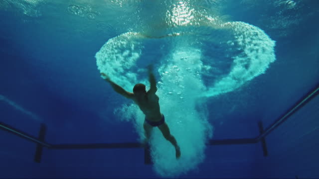 male athlete diving into swimming pool - tuffarsi video stock e b–roll