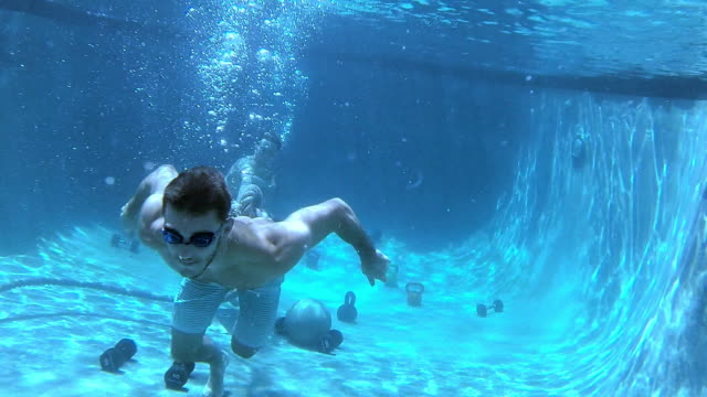 male athlete does a gym workout underwater in a pool - utebassäng bildbanksvideor och videomaterial från bakom kulisserna