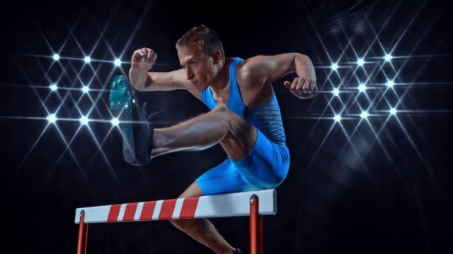 slo mo ds male athlete doing a hurdle jump at night - track and field event stock videos and b-roll footage