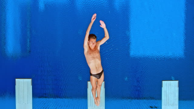 slo mo cs male athlete doing a rotation in the air while diving into the pool in sunshine - crane shot stock videos & royalty-free footage
