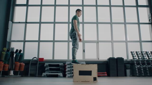 vidéos et rushes de athlète masculin faisant le saut de boîte à la gymnastique - entraînement croisé