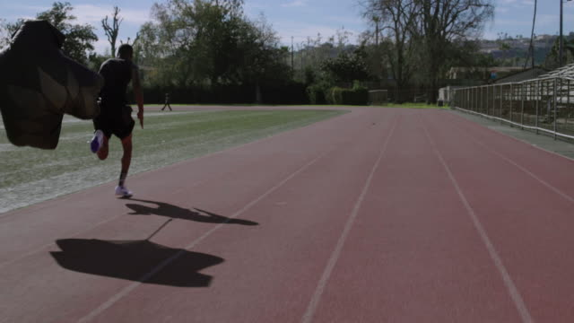 A male athlete doing speed and agility training with parachutes.