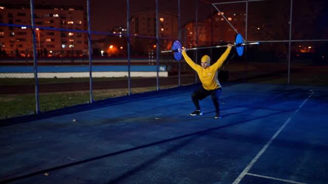 vídeos de stock e filmes b-roll de male athlete doing squats with weights outdoors at night - vida urbana