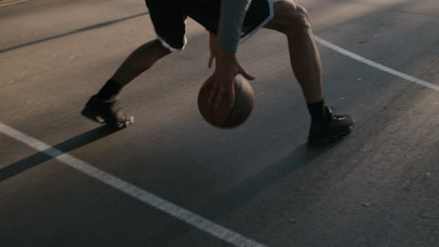 vídeos de stock e filmes b-roll de male athlete dribbling ball on basketball court - eficiência