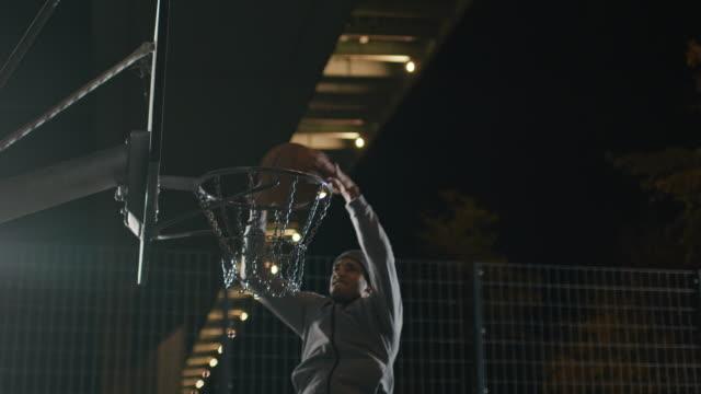 vídeos y material grabado en eventos de stock de atleta masculino dunking baloncesto en aro en la noche - mate técnica de vídeo