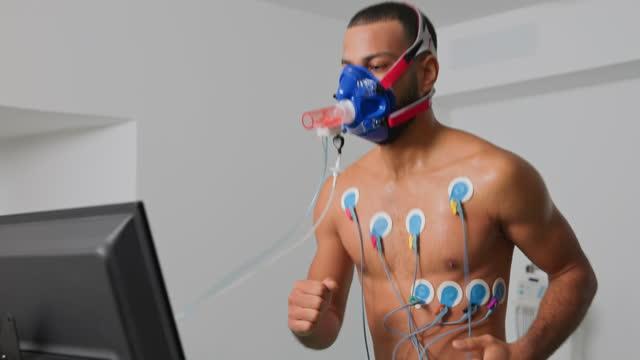 vidéos et rushes de athlète masculin de ds pendant un essai cardio-respiratoire de stress sur le tapis roulant - effort
