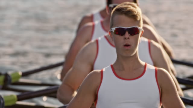 slo mo male athlete during sculling with his team mates - rowing stock videos & royalty-free footage