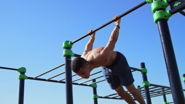 male athlete hanging on gymnastics bar at beach - hanging stock videos & royalty-free footage