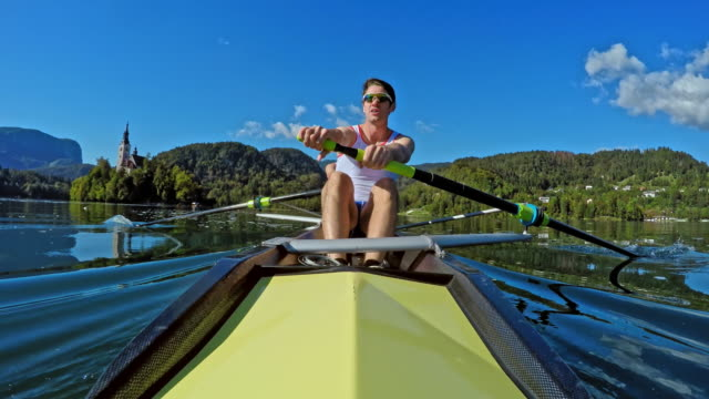 pov male athlete in a coxless pair rowing across a lake in sunshine - scull stock videos & royalty-free footage