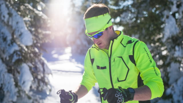 Male athlete in winter landscape, checking smart watch
