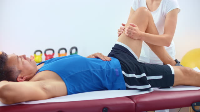 slo mo male athlete lying on the table and getting a sport massage therapy for his knee - massage table stock videos & royalty-free footage
